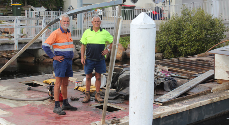 Paul Bendy and Dave Denton standing on the damaged wreck of the houseboat.