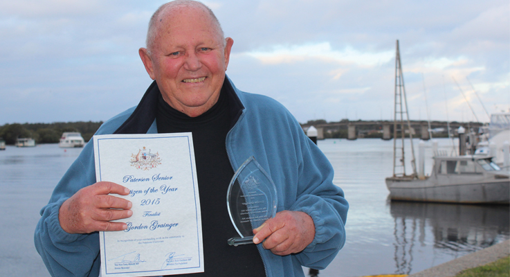 Gordon Grainger from Tea Gardens, with his awards, beside his beloved Myall River.