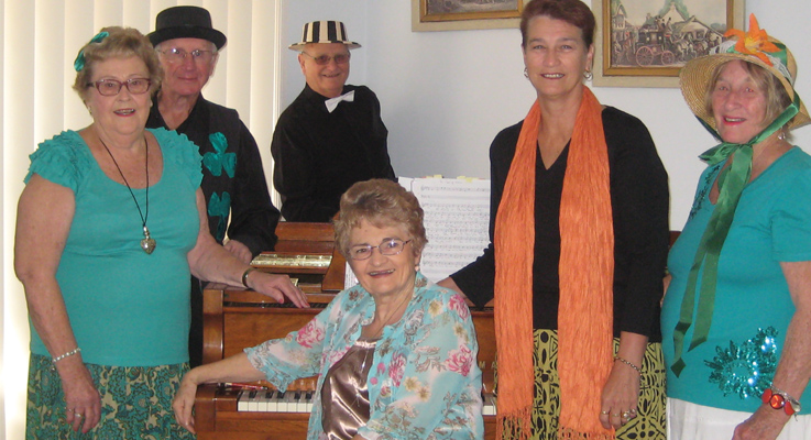 Noreen Roach, Joe Kennelly, Barry McLean, Mary Cooper, Beth Milne and Margaret Rowden seated in front at the piano.
