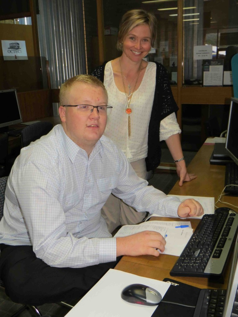 Rural Transaction Centre Customer Service Officer Kim Kent guides Douglas Martin on his first day of work.