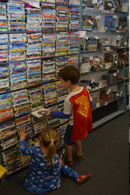 Local child, Elizabeth Kilday surveys the remaining DVDs available to purchase before the shop closes.