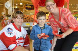 Michael Kilday receiving a red donut from Coles team member Ann Marie Stott-Lucas and Ashlee Marmont.