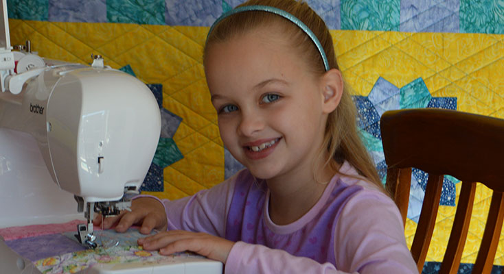 Scarlett Lewis working with her new Brother sewing machine with here 2015 quilt in the background.