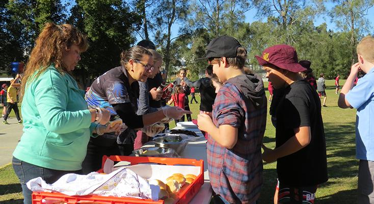 TUCKER: Students and visitors enjoy kangaroo burgers at Tea Gardens Public School.