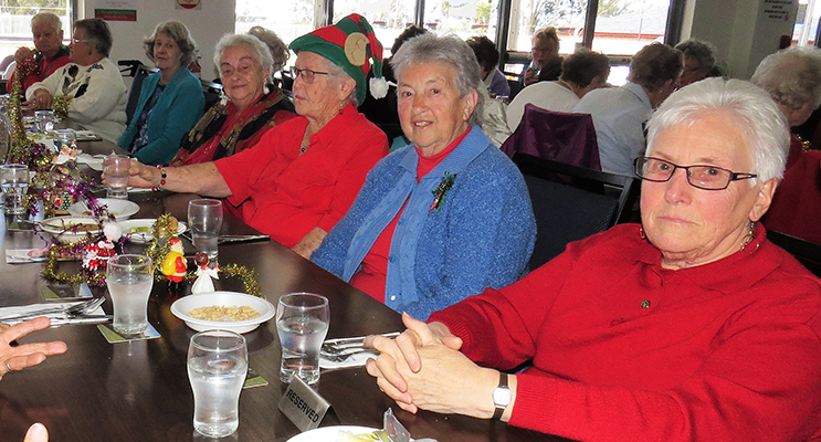 CHRISTMAS SPIRIT: Bulahdelah Neighbour Aid group membersdressed in Christmas red.