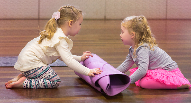 Rolling up the yoga map, Isabelle (left) and Cora.