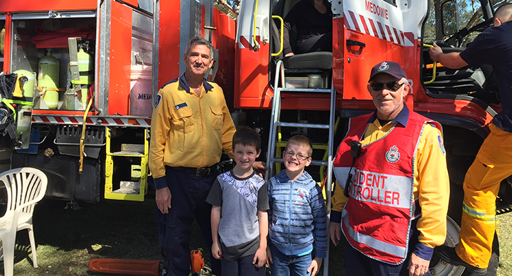 Thomas and Robert Wilks being shown a fire truck by Brigade members Alex Van Huisstede and John Pociask.