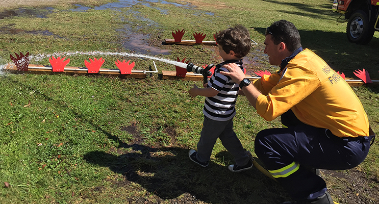 A mini fire fighter aims at the hose target to put out the flames.