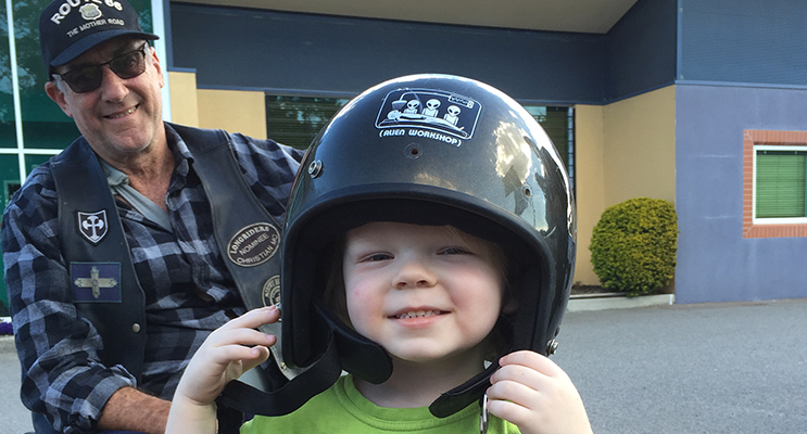 Three year old Xavier trying on a helmet for size with his new friend, Longrider member, Wheels.