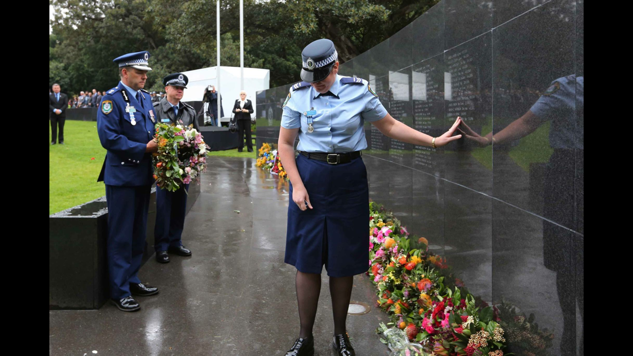 Margi,  widow of Geoffrey Richardson, places her hand on her husband's name on the Police Wall of Remembrance.