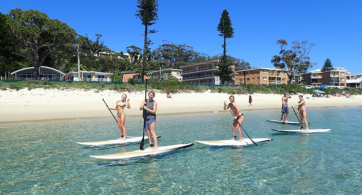 Nicole Maslowski, Mackenzie Glover, Madison Dodds and Ella Douglas enjoying SUP at Shoal Bay Beach. Photo: SUP Shoal Bay