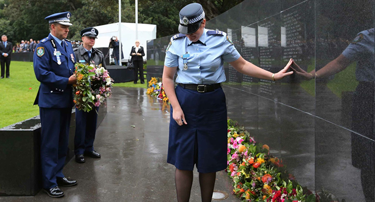 3.Margaret Richardson places her hand on her husband's name on the wall of Remembrance