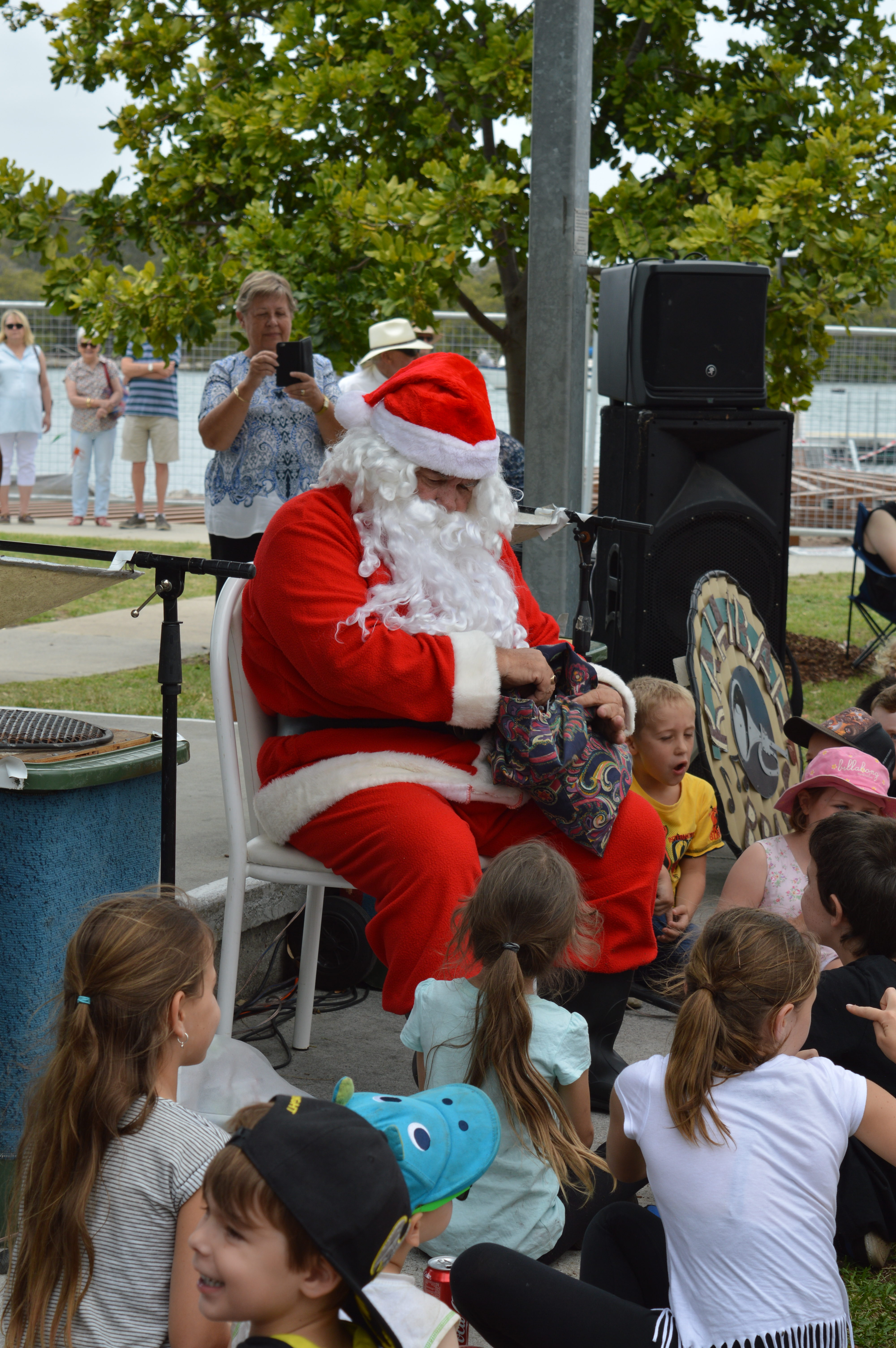 Santa hands out sweets to children after arriving on a Marine Rescue NSW boat.
