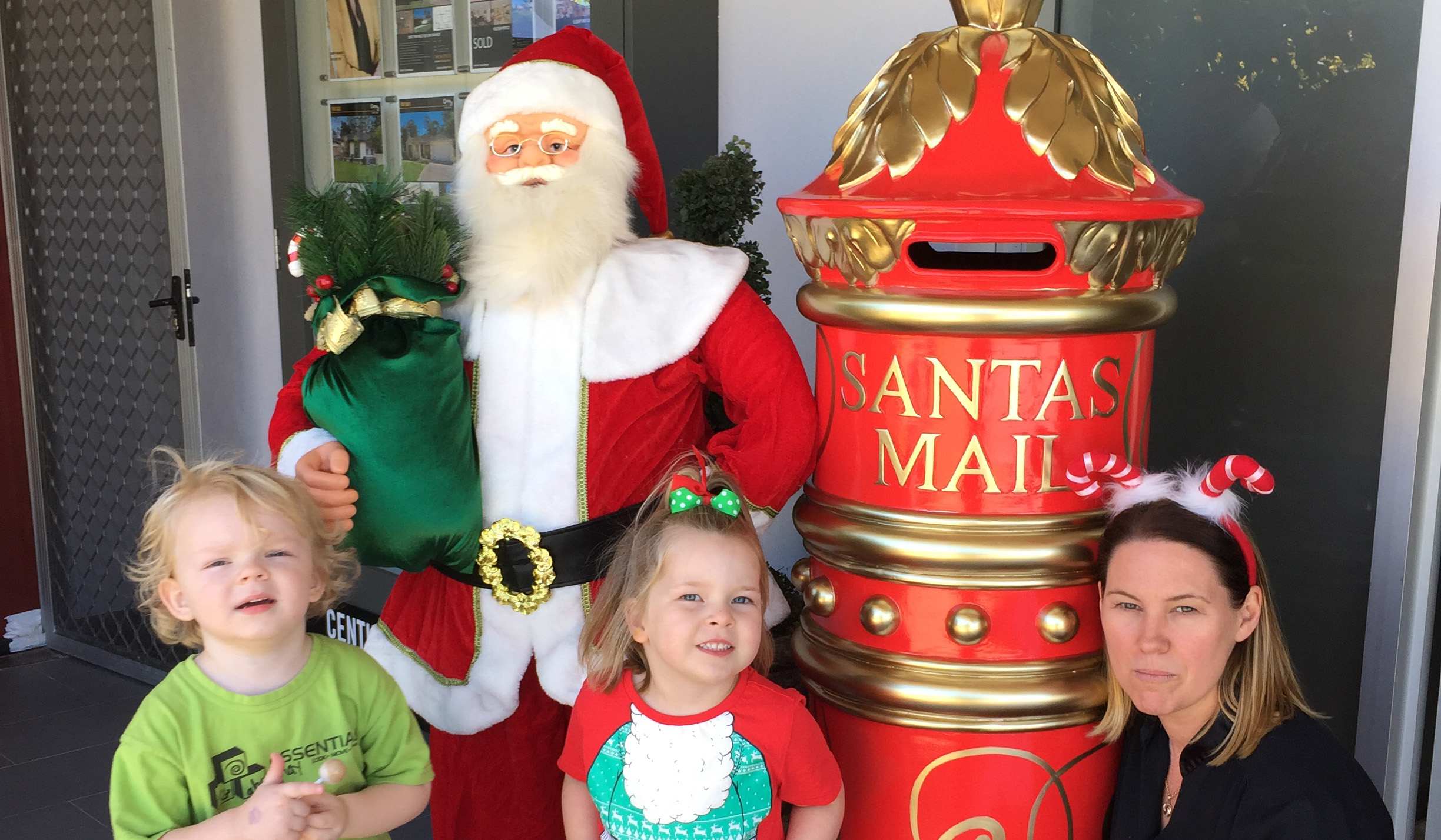 Xavier Vaughan and Evie Jeffery delivering their letter to Santa with Jane Blair from Century 21.