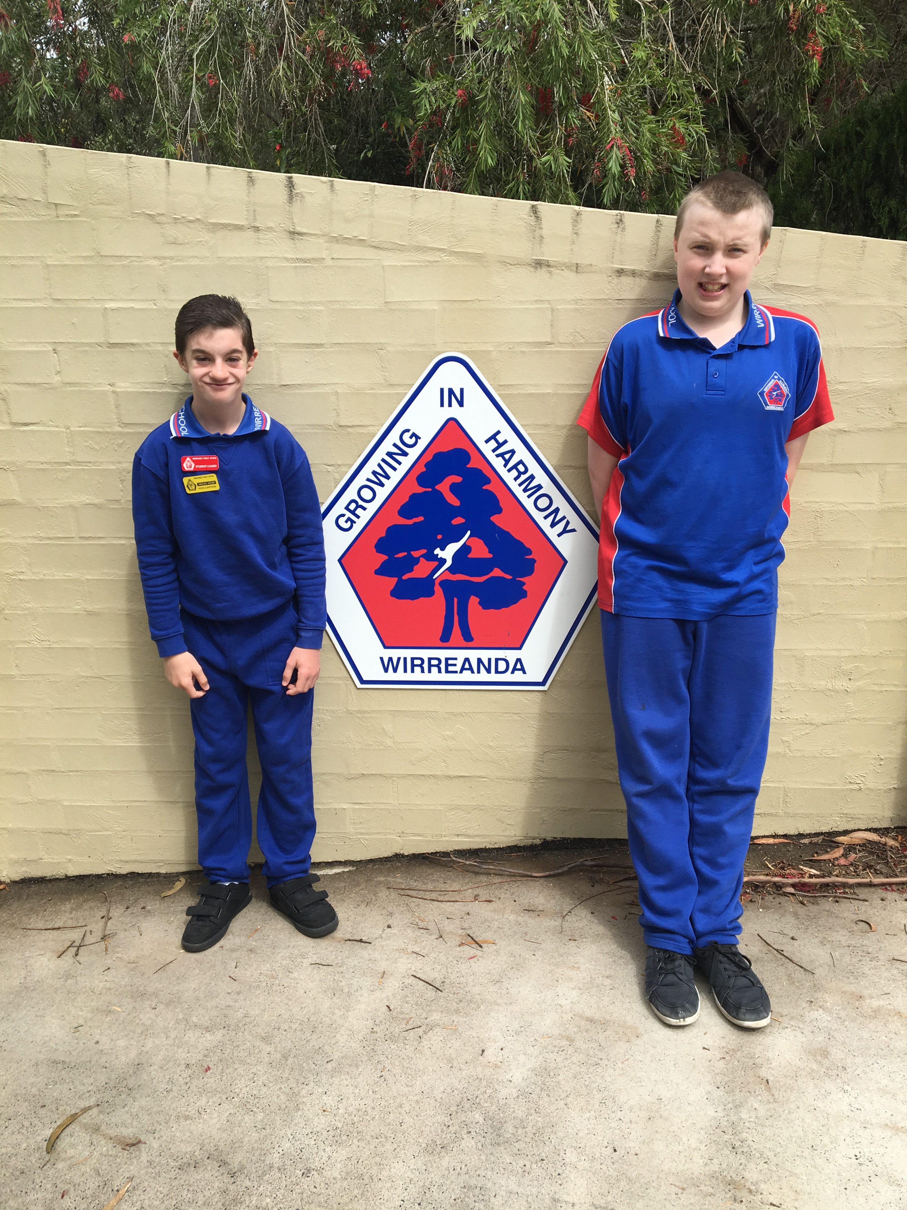 Otto van de Wijgaart and Joel Cunningham standing next to the Wirreanda Public School crest.