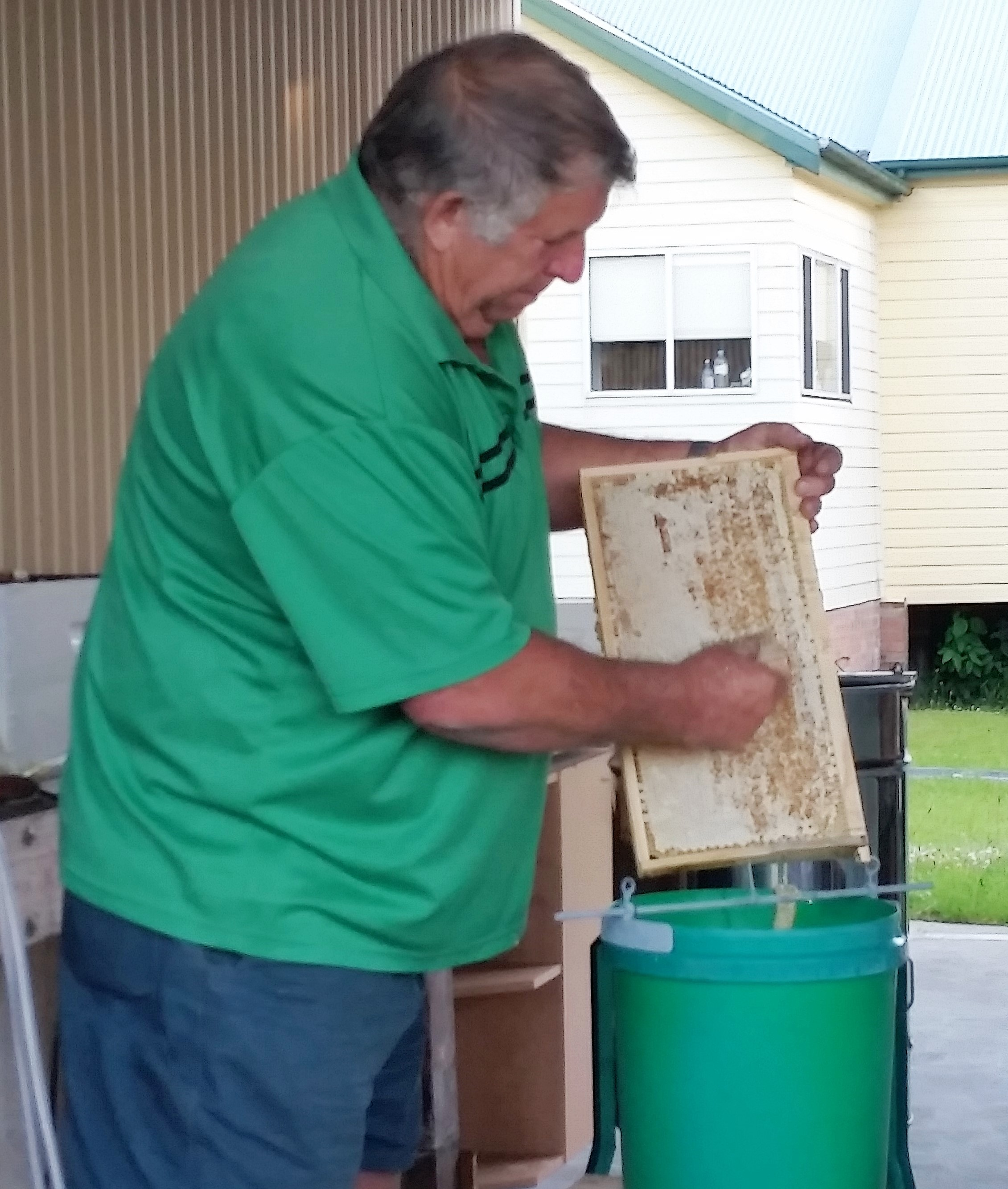 HONEY: Gary Haynes uses a scraper to remove the wax