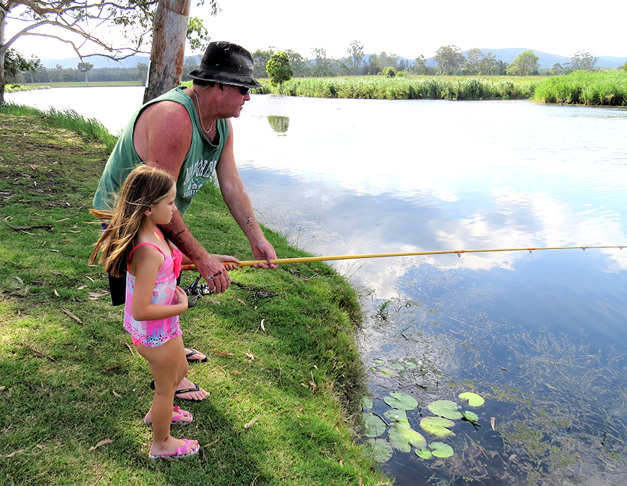 FAMILY FISHING: Brett Shultz helps Grace McRae cast a line along the banks of the Myall River