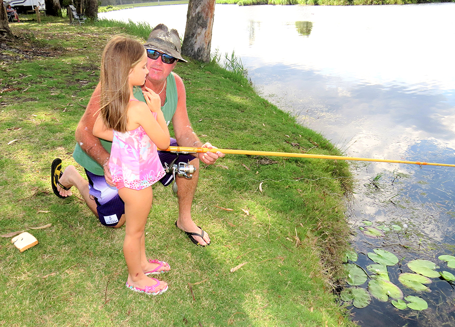 FAMILY FISHING: Brett Shultz helps Grace McRae cast a line along the banks of the Myall River.