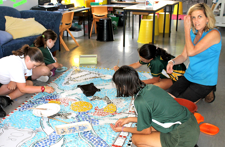 ARTWORK: Teacher Mrs Henry and students working on the mosaic.