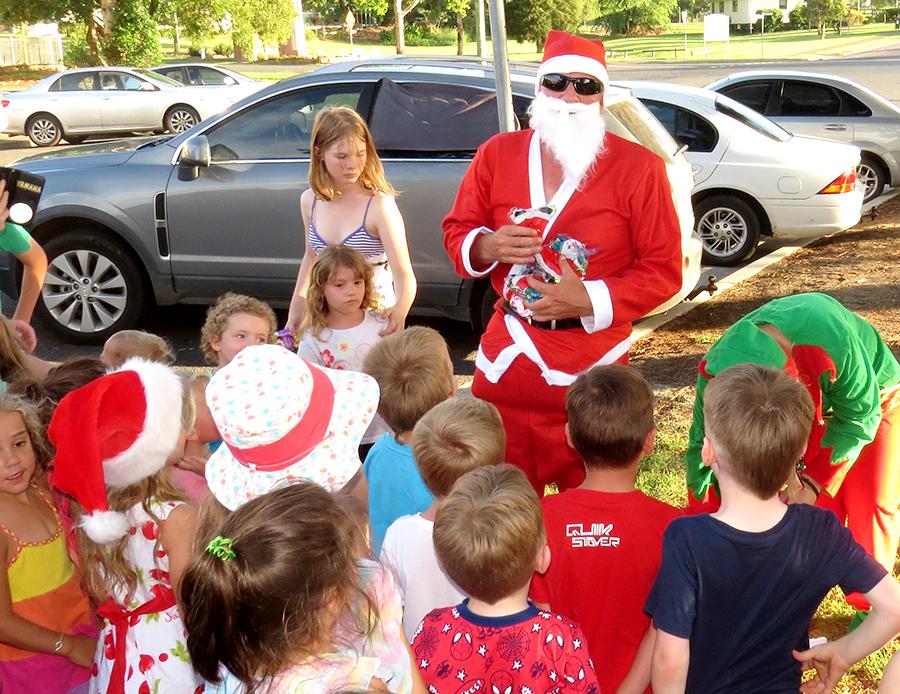 COMMUNITY SPIRIT: SANTA distributes Christmas treats to the children.