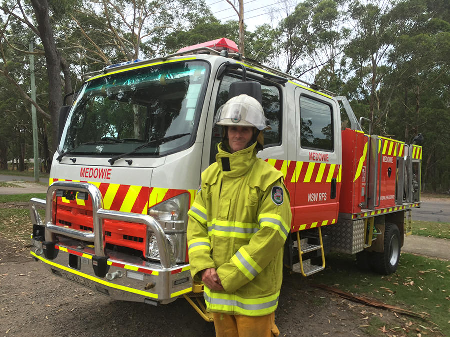 Darryl Luck in his Medowie RFS gear with one of the Brigade trucks.