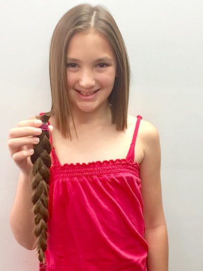Anjah Jedniuk holding her selfless donation - 36cm of hair for children with cancer.