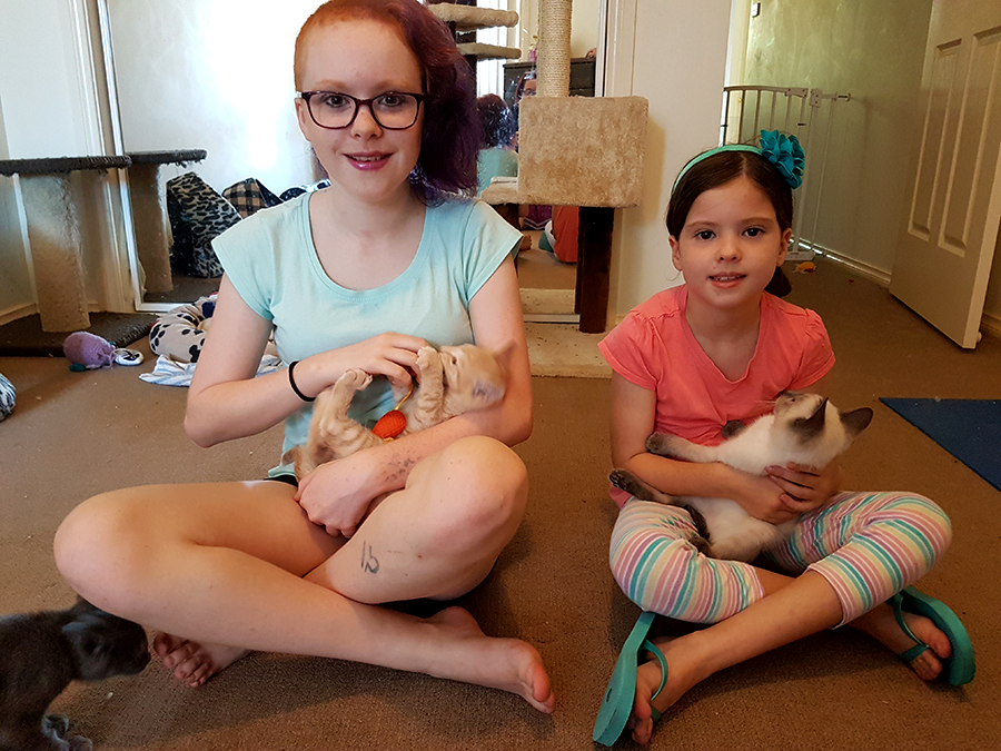 Izzy, 13 and Rhiannon, 7 cuddle the kittens.