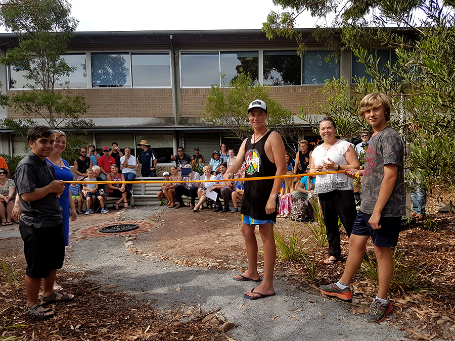 Cody Pools cuts the ribbon, assisted by Ethan Martin and Elijah Groves.
