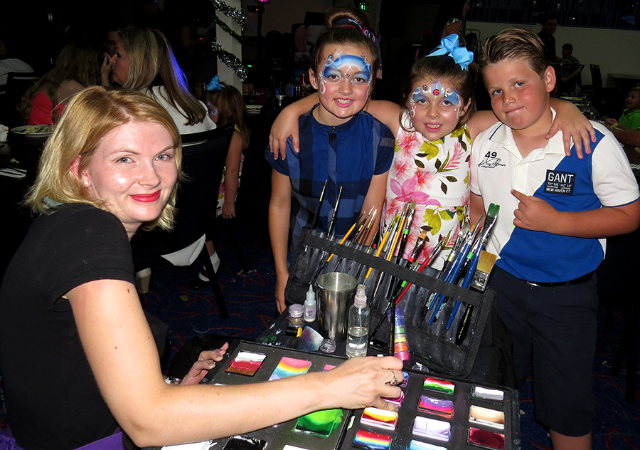 FAMILY FUN: Face painter Tennille Koelma from Rock Sloth with Margaret Stewart, Jacqueline Stewart and Riley Devine at Karuah RSL Club.