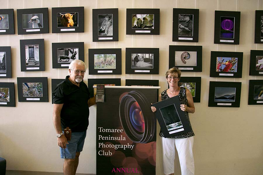 President Rudy Fuentez with Events Coordinator Vikki Ferrier changing the images on display at Tomaree Library.  Photo by Mandy Ellis