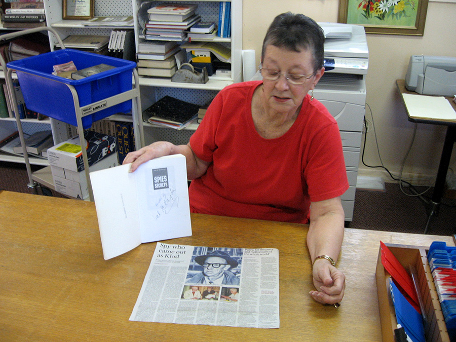 Lemon Tree librarian Marcia Lancaster with the signed book and a press clipping featuring our Master Spy.