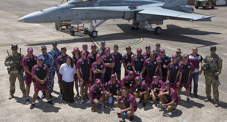 NRL Indigenous U16 team viewing Air Force assets at RAAF Base Williamtown including an F/A-18 Hornet aircraft with a Panther Fire Truck and Bushmaster vehicle.