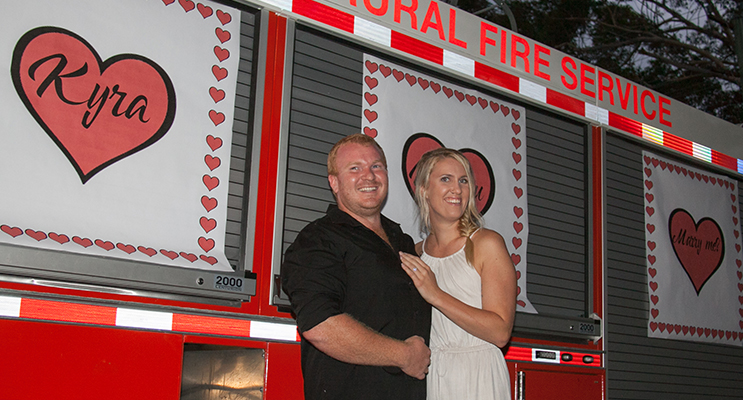 "Harrison and Kyra in front of a brigade truck emblazoned with 'Kyra will you marry me""."