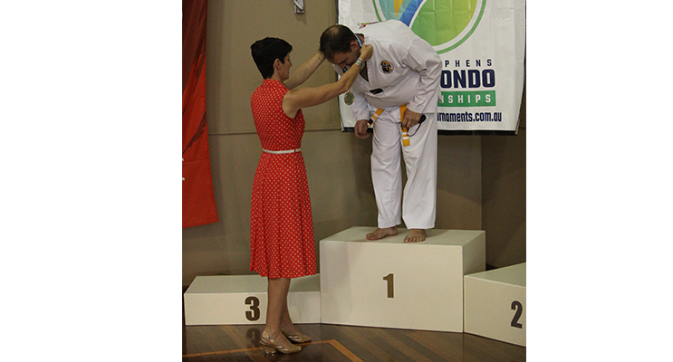 Kate Washington presenting a medal at Port Stephens Taekwondo Championships.