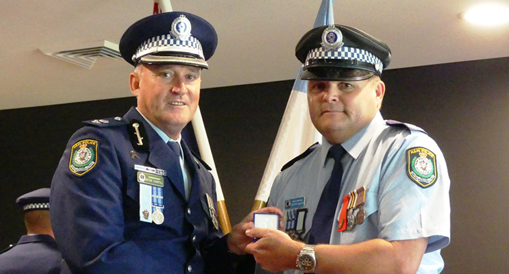 : Manning Great Lakes Commander Peter Thurtell presents the NSW Police Medal to Senior Constable Trevor Mcleod. Photo Supplied