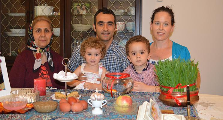 Sitting at the prepared Persian New Year table is Nasrin Aminakbari, Nima Nikfarjam, Erica Nikfarjam, with children Bernadette and Christopher.