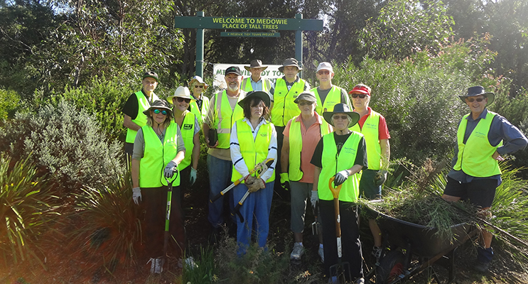 Members of the Medowie tidy towns crew with the built up, established mounds