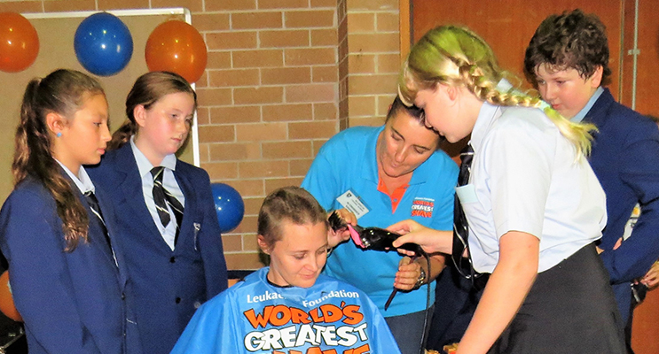 : Maggie Cunich shaves Mrs O'Connell's head with hairdresser Renee Ballantine and captains Maddi Tassell, Grace Kiehne and Oliver Gibbs.