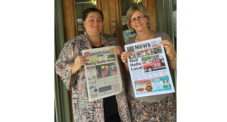 Rachael Vaughan and Lee O'Connor trade papers outside the Coonamble Times office.