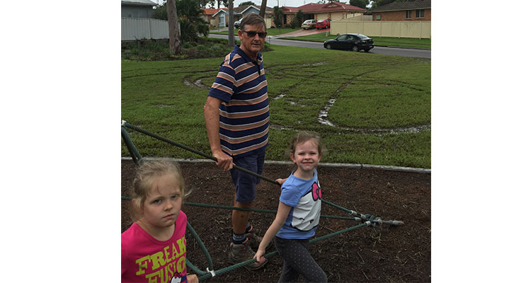 Port Stephens Councillor, Geoff Dingle with his granddaughters Jess and Katie, survey the damage done to the children's playground on Coachwood Drive.