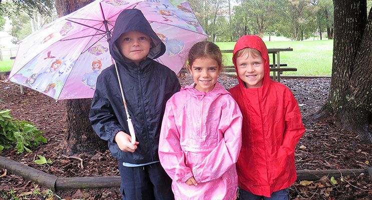More Rain to Come: Zac Moran, Abbiegail Ray and Andrew Kent prepared with their raincoats and umbrella.