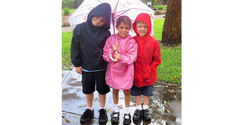 Raincoats and Umbrella: Zac Moran, Abbiegail Ray and Andrew Kent keep dry on a wet day in March.