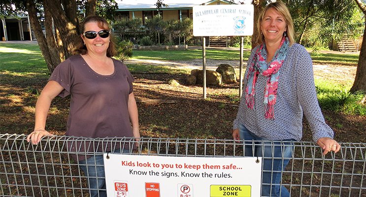 Know The Rules: BCS Deputy Principal Deb Gilbert and parent Melissa Smith, with a sign displaying the school zone traffic rules.