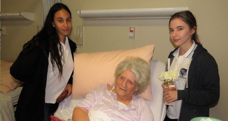 Year 12 students Leah Slockee and Katelyn Sibert visit with resident Hilda Spears.