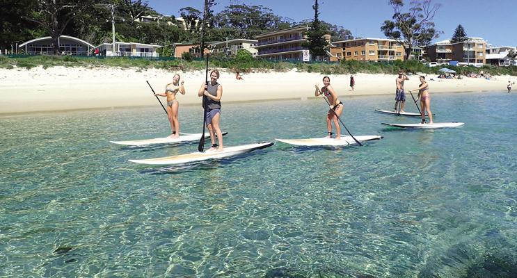 Nicole Maslowski, Mackenzie Glover, Madison Dodds and Ella Douglas enjoying SUP at Shoal Bay Beach. Photo: SUP Shoal Bay