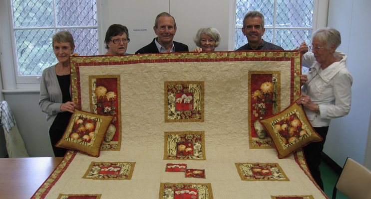 Keith Norris (centre) with the quilt dedicated to the memory of his late wife Joyce.