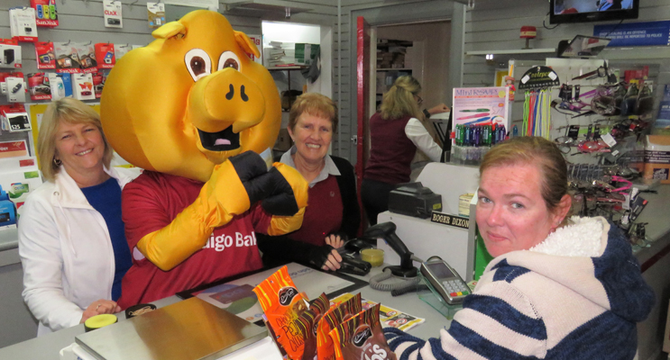 Piggy the Mascot serves Kristie Barden, assisted by Post Office staff Leanne Wright and Shirley Martin.