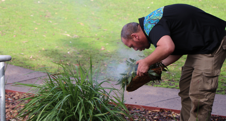 Brett Chambers, from the Worimi Green team, performing a smoking ceremony at the official opening.
