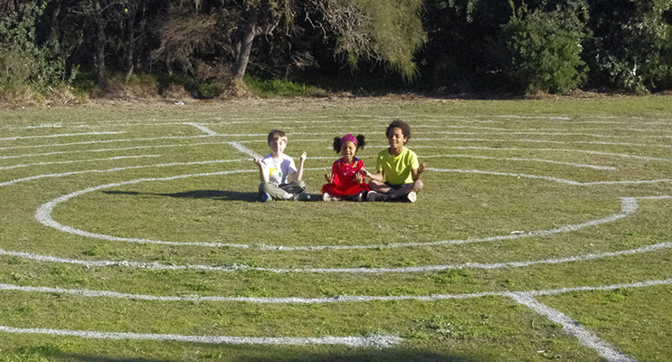 William Farrelly, Abi and Tobi Olatunde of Boat Harbour meditate in the centre of the labyrinth.