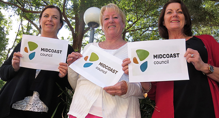 Local residents Linda Drenkhahn, Jennifer Hughes and Julie Worth examine the new MidCoast logo.